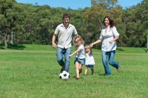 Happy family playing with a soccer ball