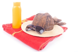 Beach hat and sunglasses on towel isolated on white background